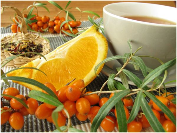 кружка чая на фоне облепихи и апельсина