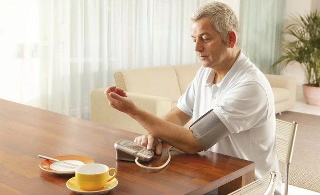 мужчина с тонометром и чашка чая